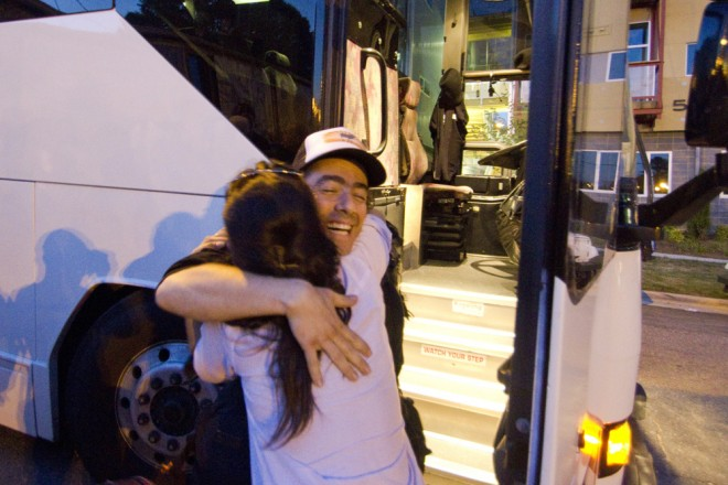 A volunteers hugs a protester from Occupy Wall Street as people arrive from out of town and out of state on busses. 5/7/12